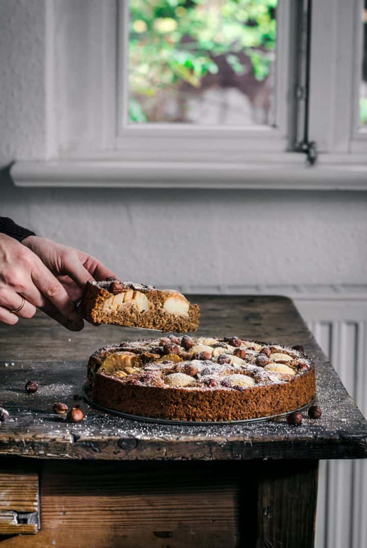hands taking a slice of apple hazelnut cake